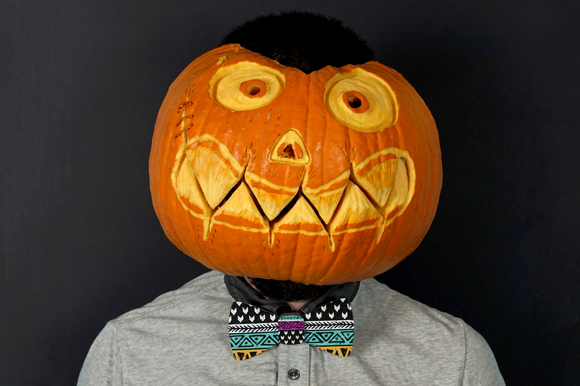 A lifestyle shot of the cardboard doodle bow tie on someone wearing a pumpkin head
